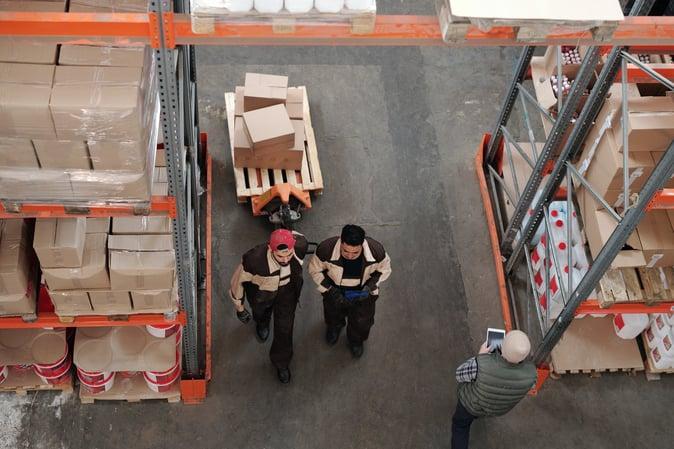 3 Men working in a shipment warehouse.
