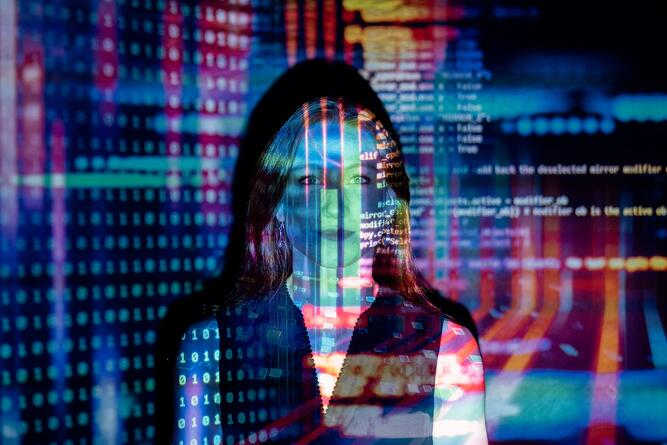 Photo of code projected over a woman