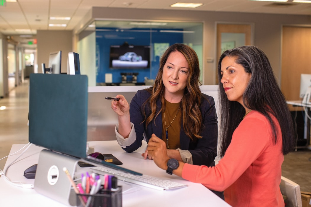 Two businesswomen assessing deductions data on a laptop.