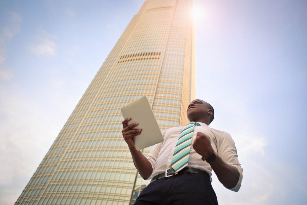 Successful businessman standing near high-rise building.