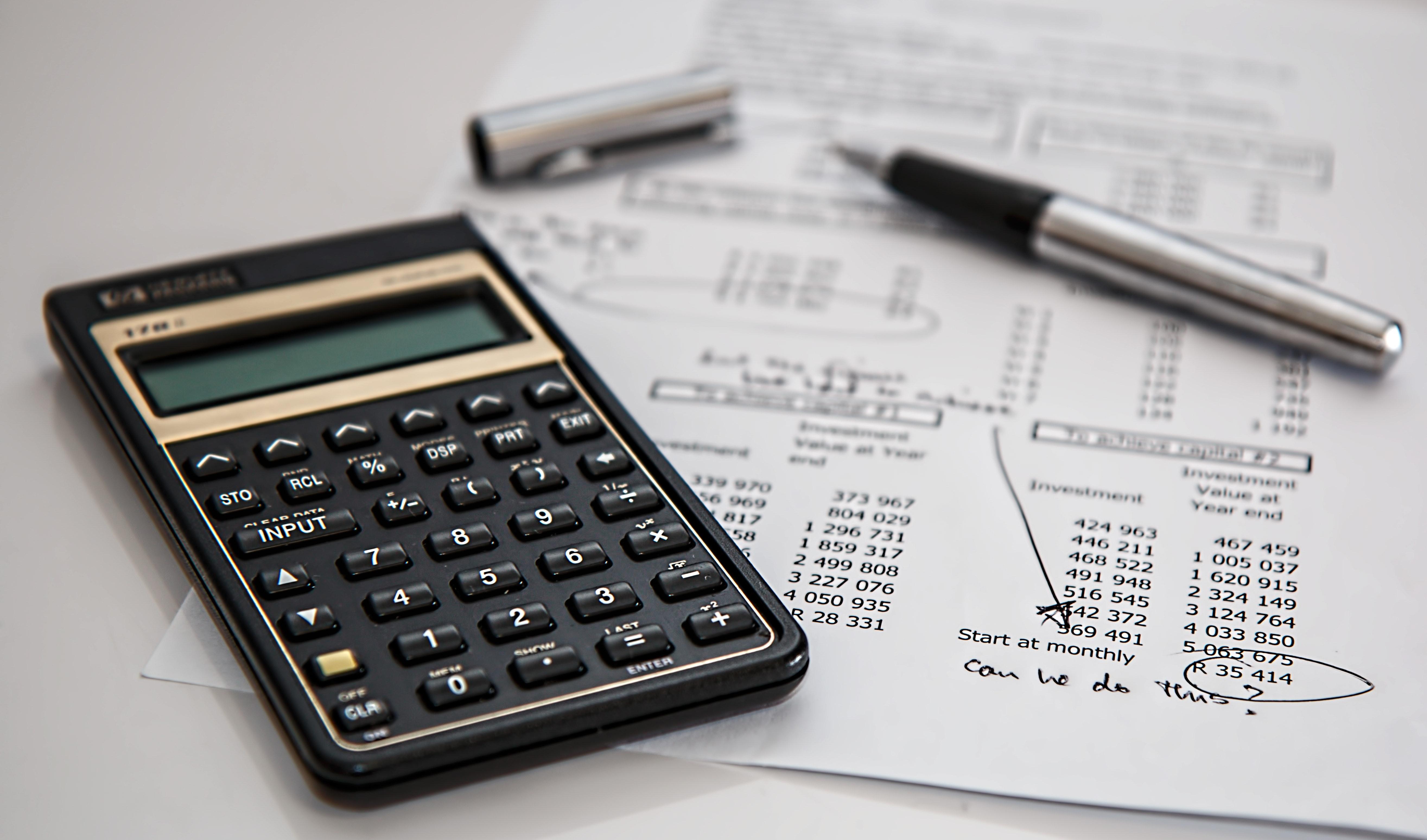 Black calculator near ballpoint pen on chargeback claim